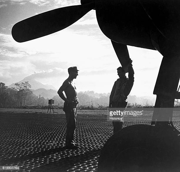 American ground crewmen at Piva strip chat next to an F4U Corsair fighter They are waiting for orders to prepare the aircraft for an impending attack...