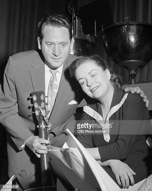 American guitarist and guitar designer Les Paul holds a guitar and puts his arm around his wife American singer Mary Ford during a rehearsal for...