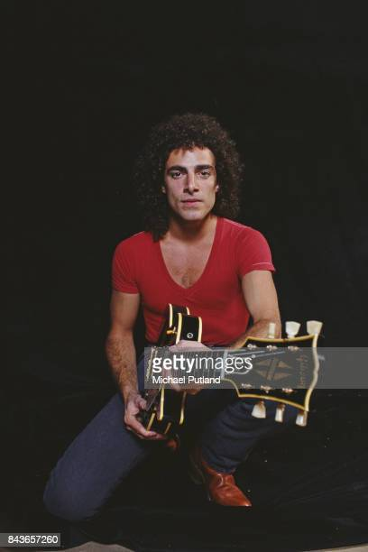 American guitarist Neal Schon of rock band Journey poses for studio portrait holding a Gibson Les Paul guitar New York 1981