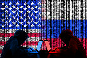 American hacker sitting opposite of a russian hacker cyberwar concept in front of binary flags