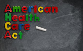 Childs magnetic letters spell American Health Care Act in congress. This is superimposed on a chalkboard or blackboard