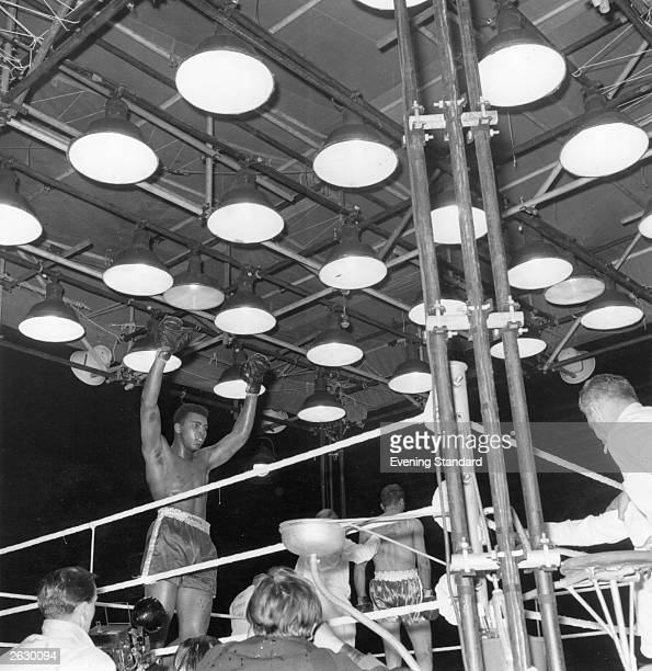 American heavyweight boxer Cassius Clay raises his arms in victory after his world title fight against British boxer Henry Cooper Original...