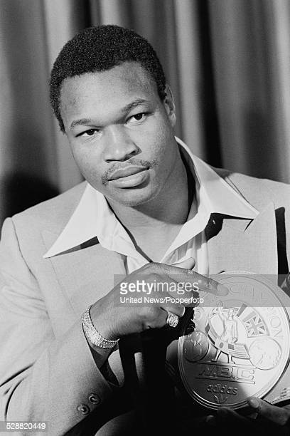 American heavyweight boxer Larry Holmes holds his WBC Heavyweight Championship belt in London on 30th June 1978