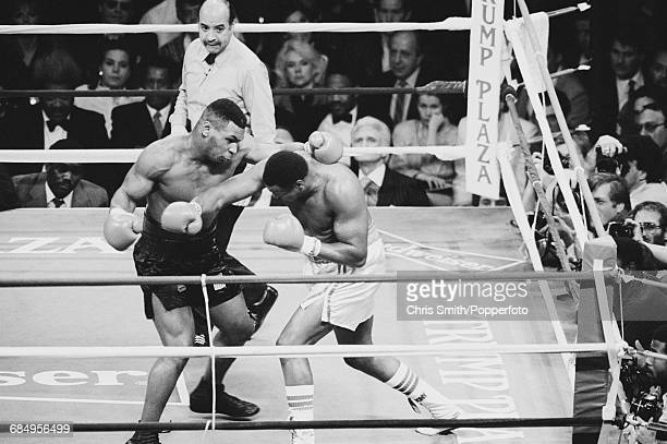 American heavyweight boxer Mike Tyson pictured left in action in his heavyweight title fight against Larry Holmes with referee Joe Cortez looking on...