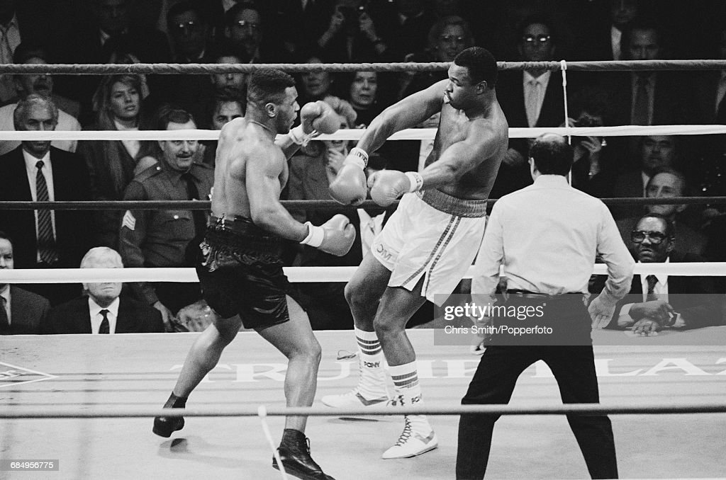 American heavyweight boxer Mike Tyson pictured left in action in his heavyweight title fight with Larry Holmes at the Convention Hall in Atlantic City, United States on 22nd January 1988. Mike Tyson would go on to defeat Larry Holmes with a TKO in the fourth round to retain his WBA, WBC and IBF titles.