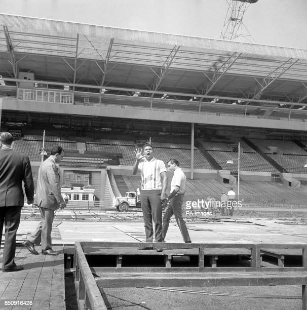 American heavyweight Cassius Clay holds up five fingers at Wembley Stadium London in reiteration of his boast that he will put Henry Cooper away in...