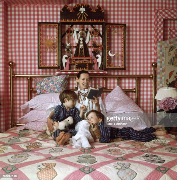 American heiress and socialite Gloria Vanderbilt reads to her two sons Carter and Anderson on a bed in their home Southampton Long Island New York...