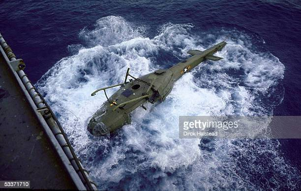 American helicopter sinking after being dumped overboard from aircraft carrier to make more room for the evacuation of American personnel from...