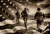 Three Active Duty American Soldiers Running Through a horizontal image of a field of stars and stripes.  Battle ready and running.  Sepia Toned.  Grain.  I have a color image if asked.  Composite Imag
