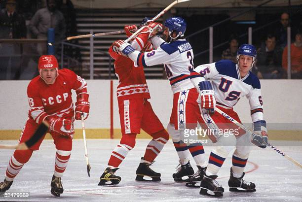 American hockey player Ken Morrow of Team USA hits a member of the CCCP team as another Soviet and Morrow's teammate Mike Ramsey keep an eye on the...