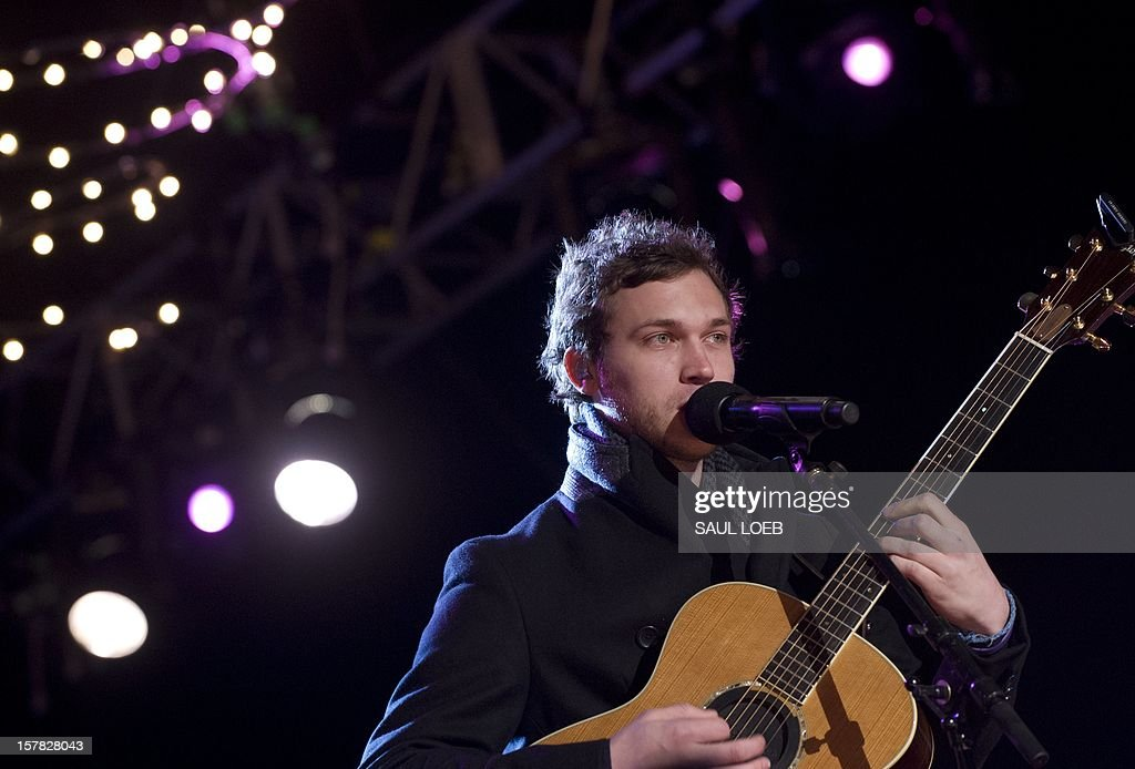 American Idol season 11 winner Phillip Phillips performs during the National Christmas Tree Lighting on the Ellipse adjacent to the White House in Washington, DC, on December 6, 2012. The annual event, hosted by actor Neil Patrick Harris, features US President Barack Obama and performances by Jason Mraz, Ledisi, James Taylor, Kenny 'Babyface' Edmonds, Colbie Caillat and American Idol season 11 winner Phillip Phillips. AFP PHOTO / Saul LOEB
