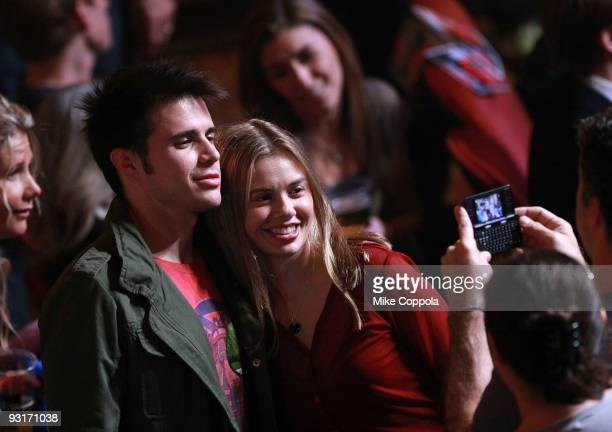 American Idol winner Kris Allen takes a picture with a fan in the audience at The Beacon Theatre on November 17 2009 in New York City