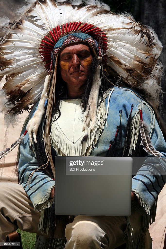 American Indian Man Wearing Traditional Dress and Using Laptop : Stock Photo