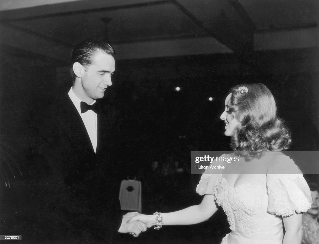 American industrialist aviator and film producer Howard Hughes shakes hands with American actress Bette Davis at the Tailwaggers party thrown by...