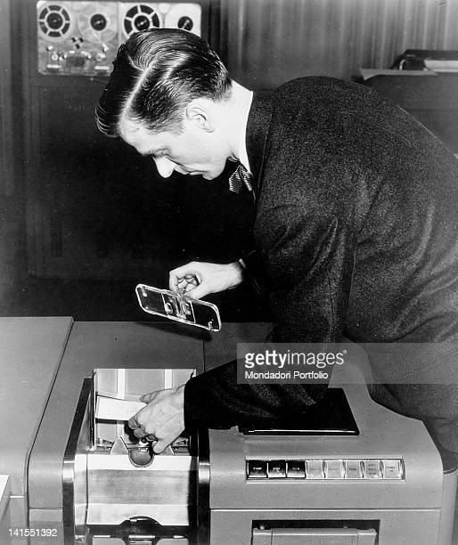 American information technologist putting some punched cards into the reader of an IBM701 electronic calculator USA 1960s