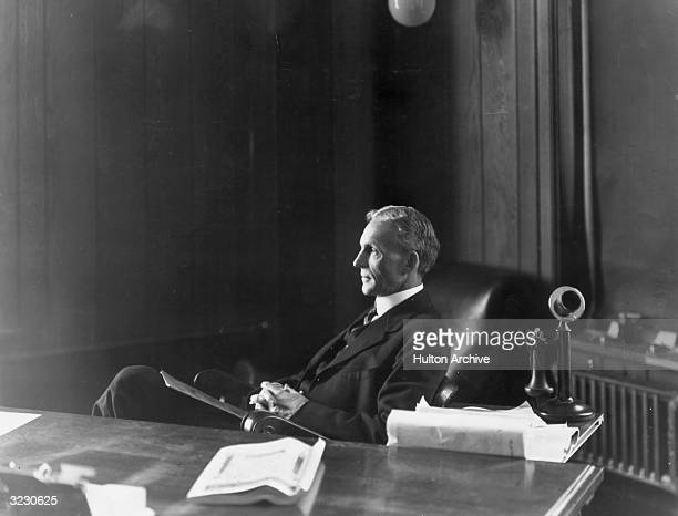 American inventor and industrialist Henry Ford sitting at his desk in his office in Highland Park Michigan