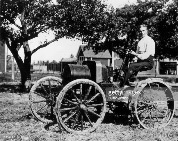 American inventor and manufacturer Henry Ford drives an early tractor which he called an 'automobile plow' powered by a 1904 ModelB type engine on...