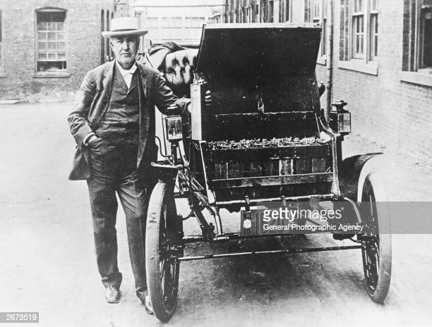 American inventor and physicist Thomas Edison with his first electric car the Edison Baker He is holding one of the batteries used to power the...