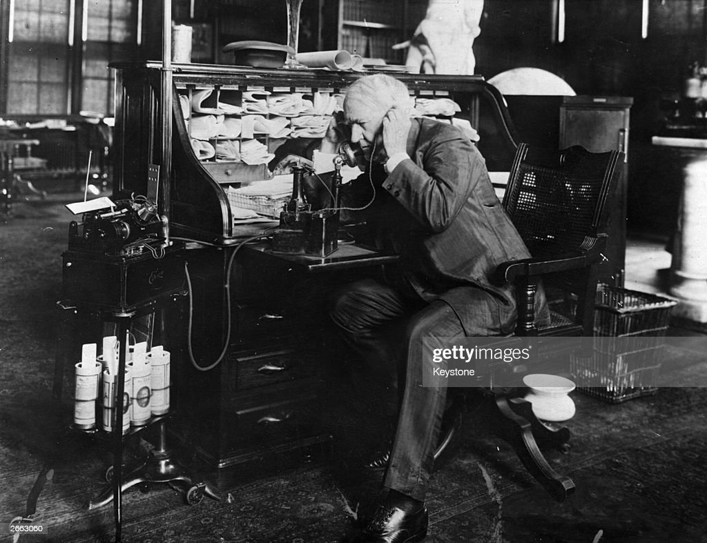 American inventor Thomas Edison (1847 - 1931) dictating instructions to an employee on his 'telescribe' dictating machine.