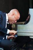 American jazz musician Aaron Diehl plays piano as he leads his quartet at the 21st Annual Charlie Parker Jazz Festival in Tompkins Square Park New...