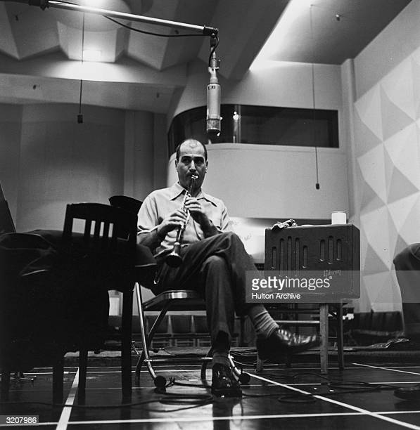 American jazz musician and bandleader Artie Shaw plays a clarinet while seated near a microphone in a recording studio mid 1950s