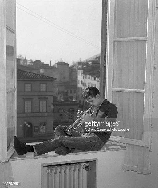 American jazz musician Chet Baker playing trumpet on a window ledge in Lucca 1961