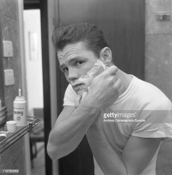 American jazz musician Chet Baker reflected in a mirror while shaving shaving foam on his face Lucca 1961