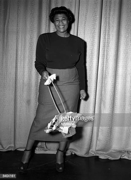 American jazz scat singer Ella Fitzgerald swinging a basket