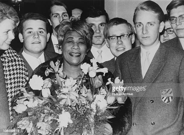 American jazz singer Ella Fitzgerald is presented with a bouquet in Munich Germany during a tour 3rd April 1965