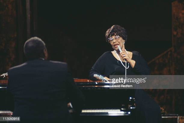 Ella Fitzgerald US jazz singer singing into a microphone while standing beside a piano being played by Oscar Peterson who has his back to the camera...