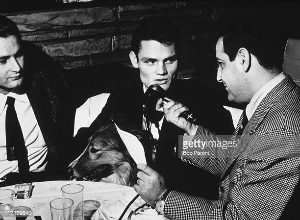 American jazz trumpeter and singer Chet Baker is interviewed by a man with a microphone whilst sitting with a collie 13th December 1954