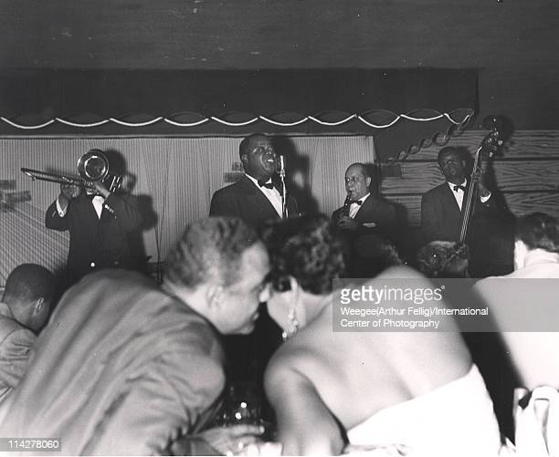 American jazz trumpeter and singer Louis Armstrong and his All Stars perform on stage at Basin Street New York New York 1940s Photo by Weegee...