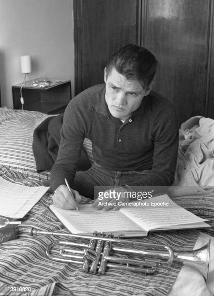 American jazz trumpeter Chesney Henry 'Chet' Baker sitting on a Lucca Hotel bed writing music with his trumpet and music paper next to him Lucca 1961