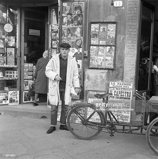 American jazz trumpeter Chesney Henry 'Chet' Baker standing in one Lucca's street in front of a newsagent and next to a tricycle wearing jeans a...