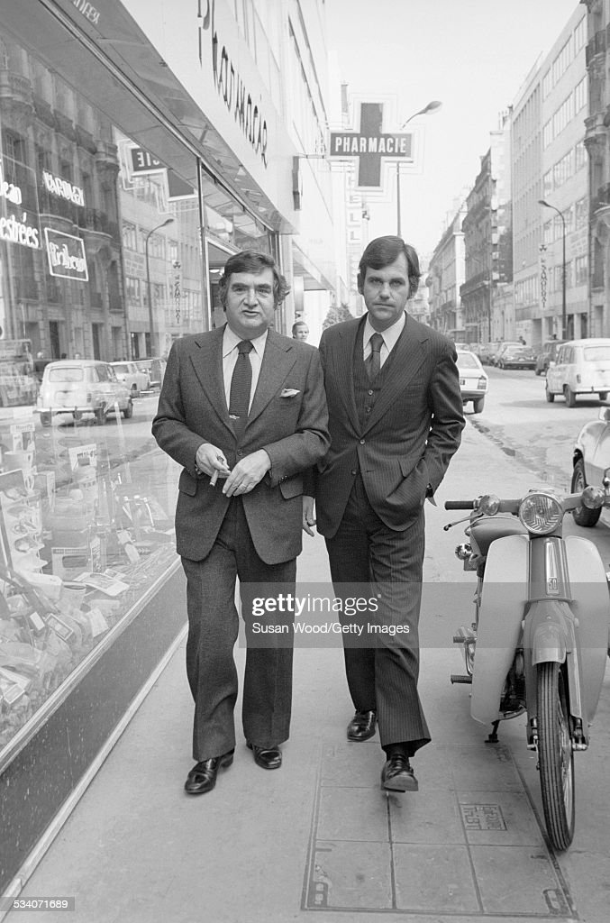 American journalist, and former US Press Secretary to President Kennedy, Pierre Salinger (1925 - 2004) (left) and American former US Press Secretary to President Nixon Ron Ziegler (1939 - 2003) walk along a sidewalk together, Paris, France, late 1970s or early 1980s.