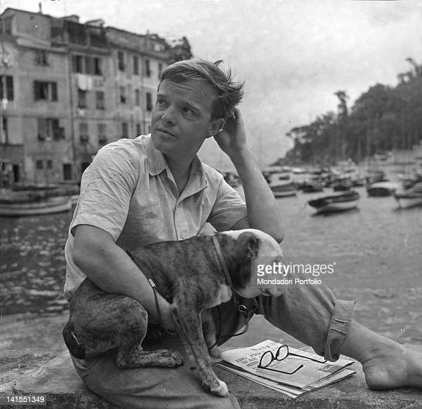American journalist and writer Truman Capote sitting on a low wall in front of the small harbour of Portofino with his bulldog in his arm Portofino...