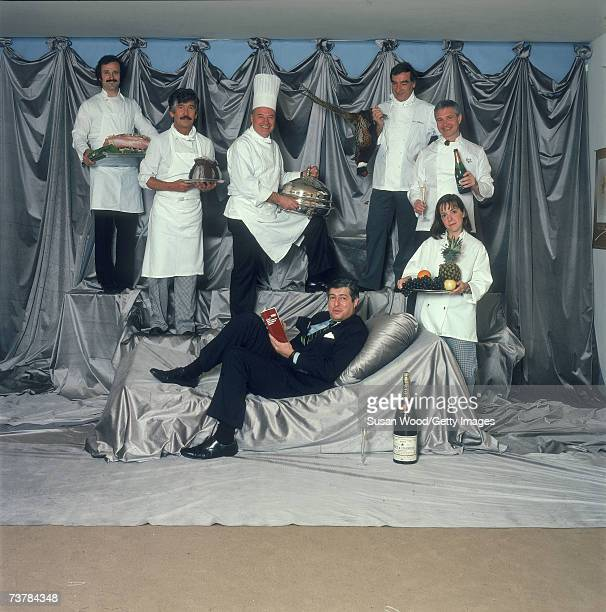 American lawyer and restaurant review compiler Tim Zagat reclines on a silver pillow as five men and a woman dressed in chef's whites stand around...