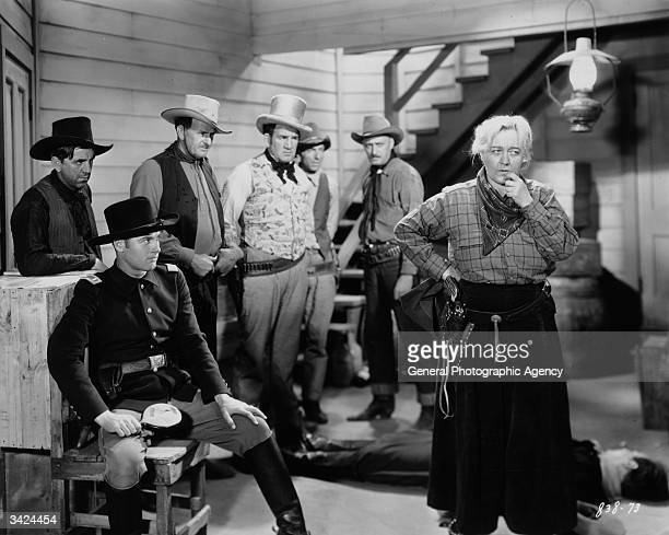 American leading man Richard Arlen born Cornelius van Mattemore sitting with a group of cowboys in a scene from the Paramount western 'Caught'...