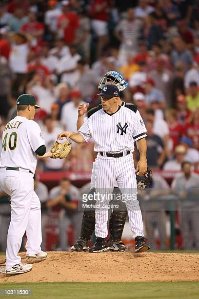 American League AllStar coach Joe Girardi of the New York Yankees handing the ball off to Andrew Bailey of the Oakland Athletics during the 81st MLB...