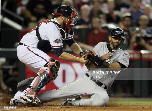 American League AllStar Jose Bautista of the Toronto Blue Jays is tagged out by National League AllStar Brian McCann of the Atlanta Braves on a throw...