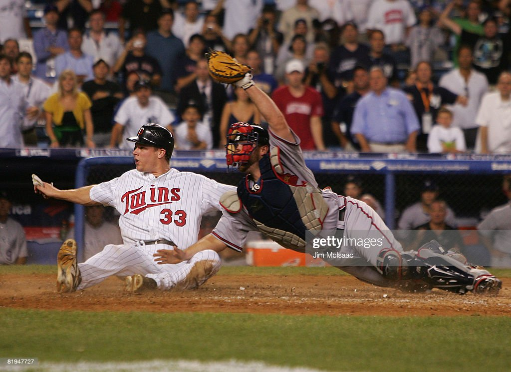 American League All-Star Justin Morneau #33 of the Minnesota Twins slides into home ahead of the tag of National League All-Star catcher Brian McCann #16 of the Atlanta Braves to win the 79th MLB All-Star Game in the 15th inning by the score of 4-3 at Yankee Stadium on July 15, 2008 in the Bronx borough of New York City.