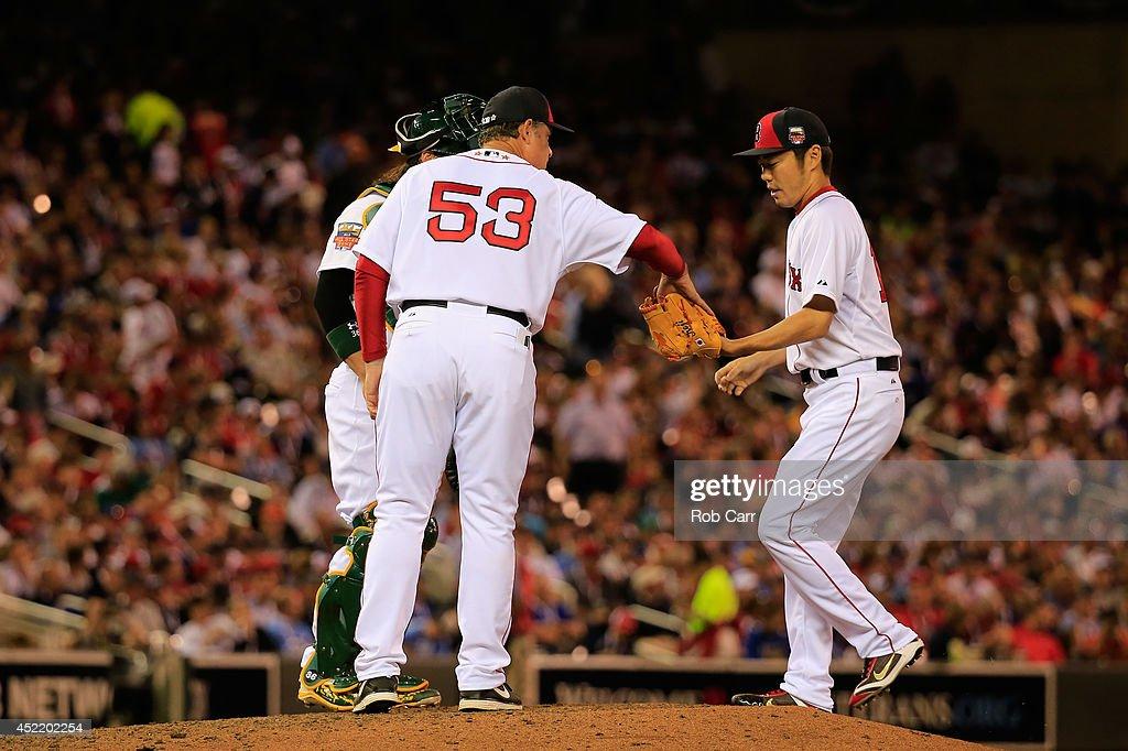 American League AllStar Manager John Farrell gives the ball to Koji Uehara against the National League AllStars during the 85th MLB AllStar Game at...