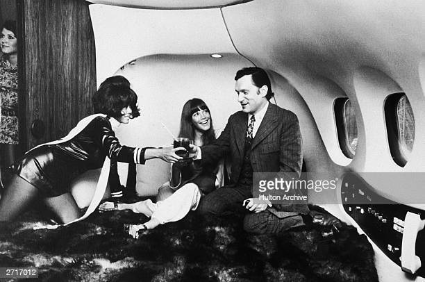 American magazine publisher Hugh Hefner and his companion American model and actor Barbi Benton relax on a bed while a stewardess attends to them in...