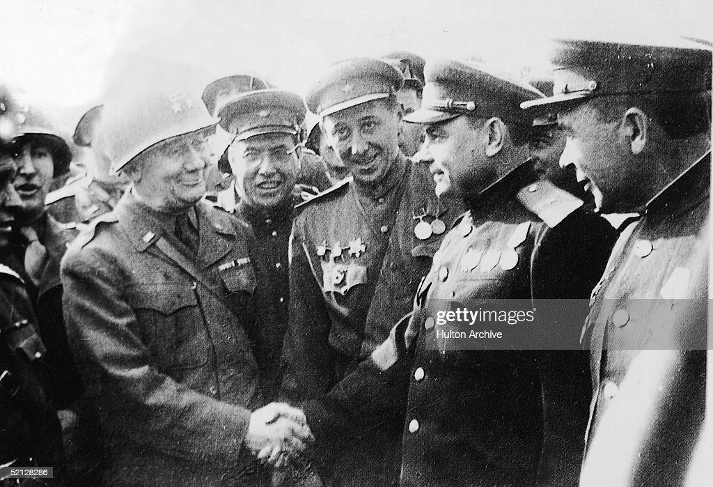 American Major-General Emil F. Reinhardt (1888 - 1969) (left), Commanding General of the 69th Division, shakes hands with his Russian counterpart, Major-General Vladimir V. Rusakov, Commanding Officer of the 58th Guards Division, at a meeting of American and Russian troops near the Elbe River and the town of Torgau, Germany, late April, 1945. The two armies had met up on the 25th of April, effectivrly splitting the opposing German army.