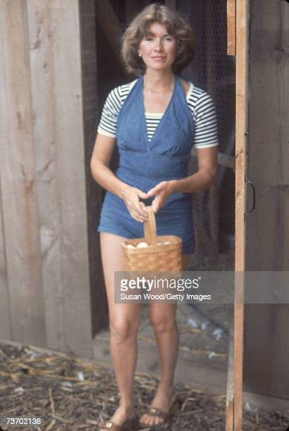 American media mogul and businesswoman Martha Stewart exits a chicken coop with a basket of eggs August 1976