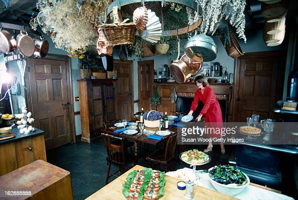 American media mogul and businesswoman Martha Stewart in a red dress sets the table in a kitchen August 1976 On the table are plates wine glasses and...