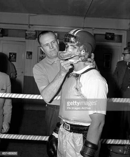 American Middleweight Don Fullmer who fights Great Britain's Terry Downes in a few days has his helmet adjusted by Manager Merv Jenson He is wearing...