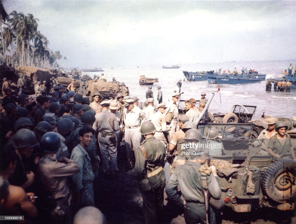 American military commander General Douglas MacArthur (1880 - 1964) (center), accompanied by Lieutenant General George C. Kenney (1889 - 1977), Lieutenant General Richard K. Sutherland (1893 - 1966), and Major General Verne D. Mudge, speaks with troops on the beach, Leyte, Philippines, October 20, 1944.