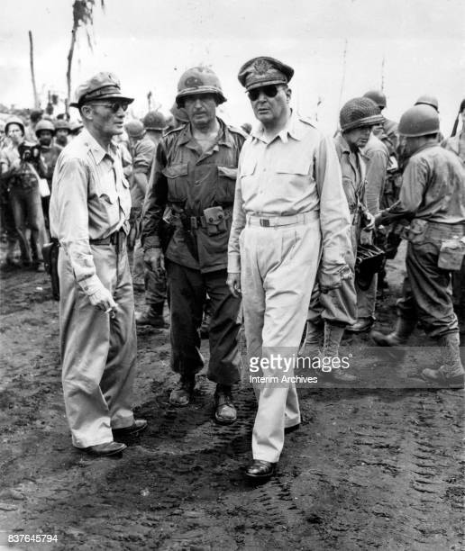 American military commander General Douglas MacArthur along with Major General Verne Mudge and others walks with US troops Leyte Philippines October...