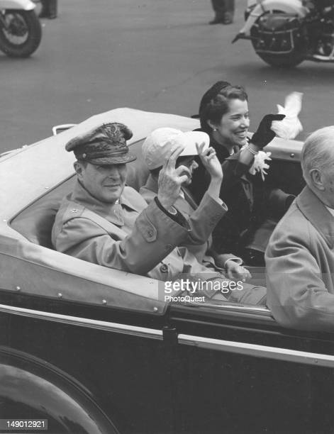 American military commander General Douglas MacArthur his son Arthur MacArthur IV and wife Jean MacArthur wave from an opentop limousine at people...